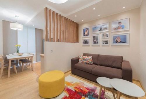 Phòng khách được bố trí đơn giản với chiếc sofa dài kê sát tường cùng bàn trà nhỏ.
